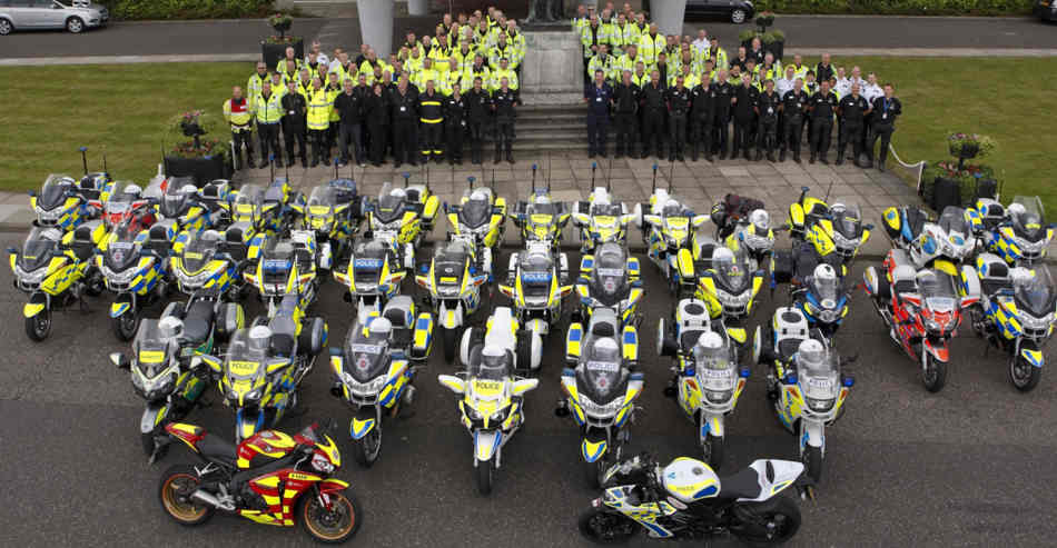 Aerial shot of a large number of police motorcyclists, standing on the steps of a large house, with the bikes lined up in front of them.