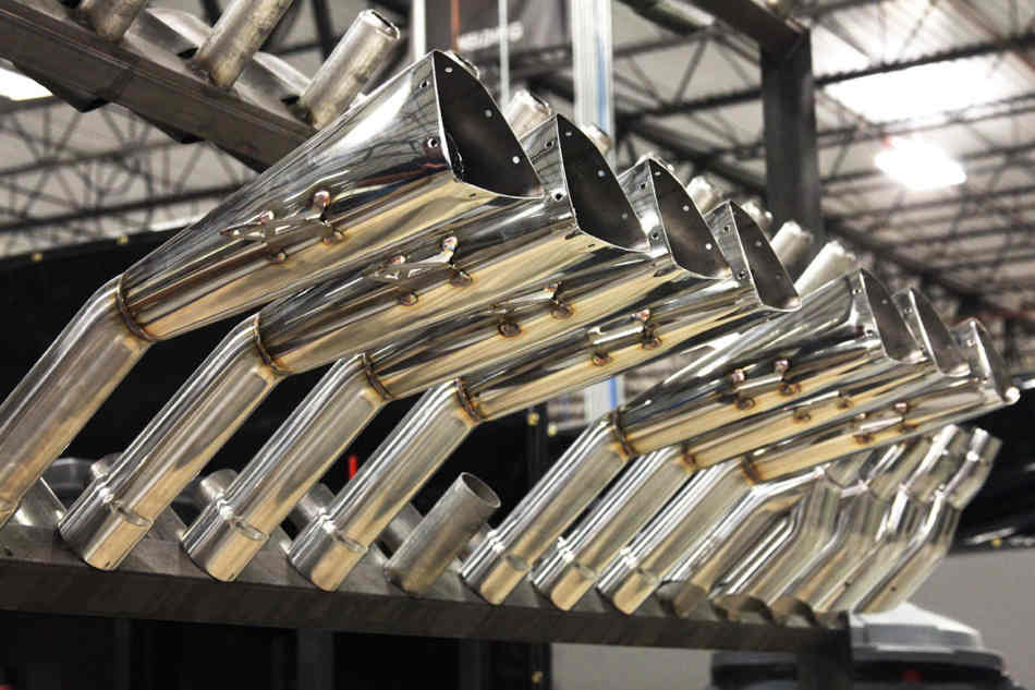 A rack of part finished motorcycle exhaust cans on a production line