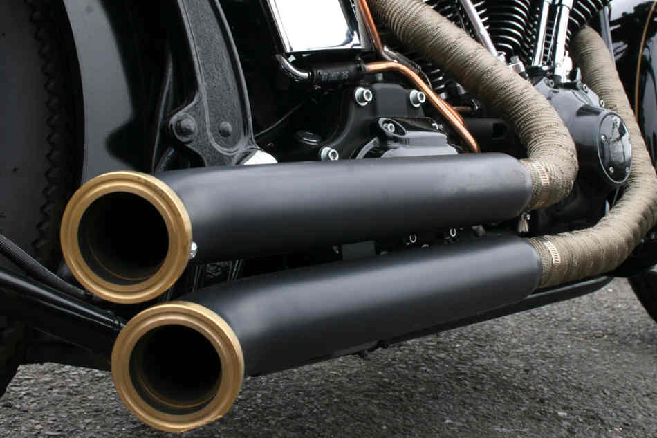 Close up of a set of custom Harley-Davidson exhaust pipes, the headers wrapped in lagging to protect the rider.