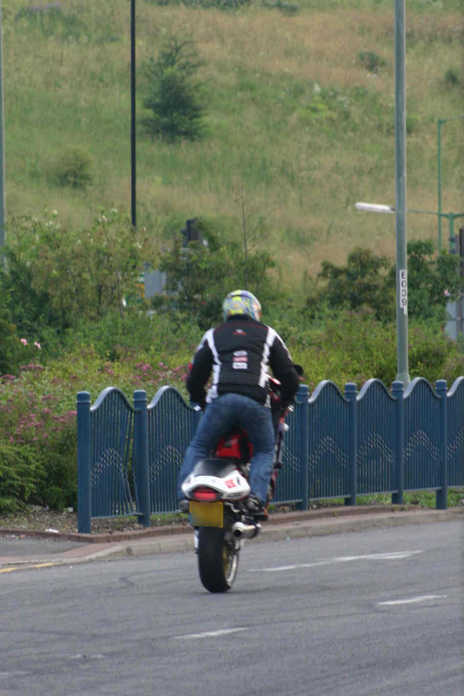 chap in jeans and a bomber jacket pulling a wheelie on a race replica sports bike on the public road.