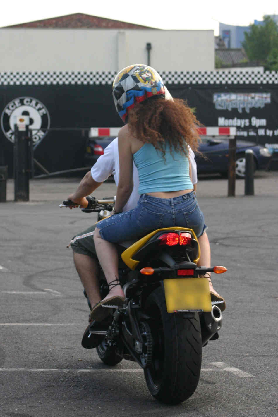 Couple riding a sports bike in the car park of the Ace cafe, London, wearing t-shirts, shorts and sandals.