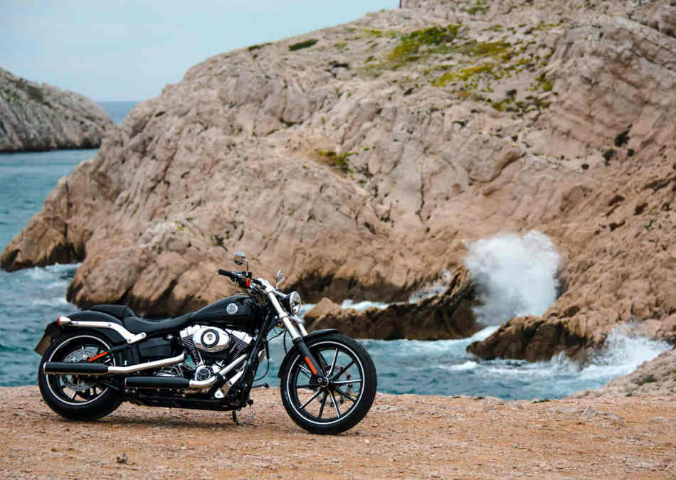 The Breakout parked on a beach with waves crashing on a cliff face behind it.