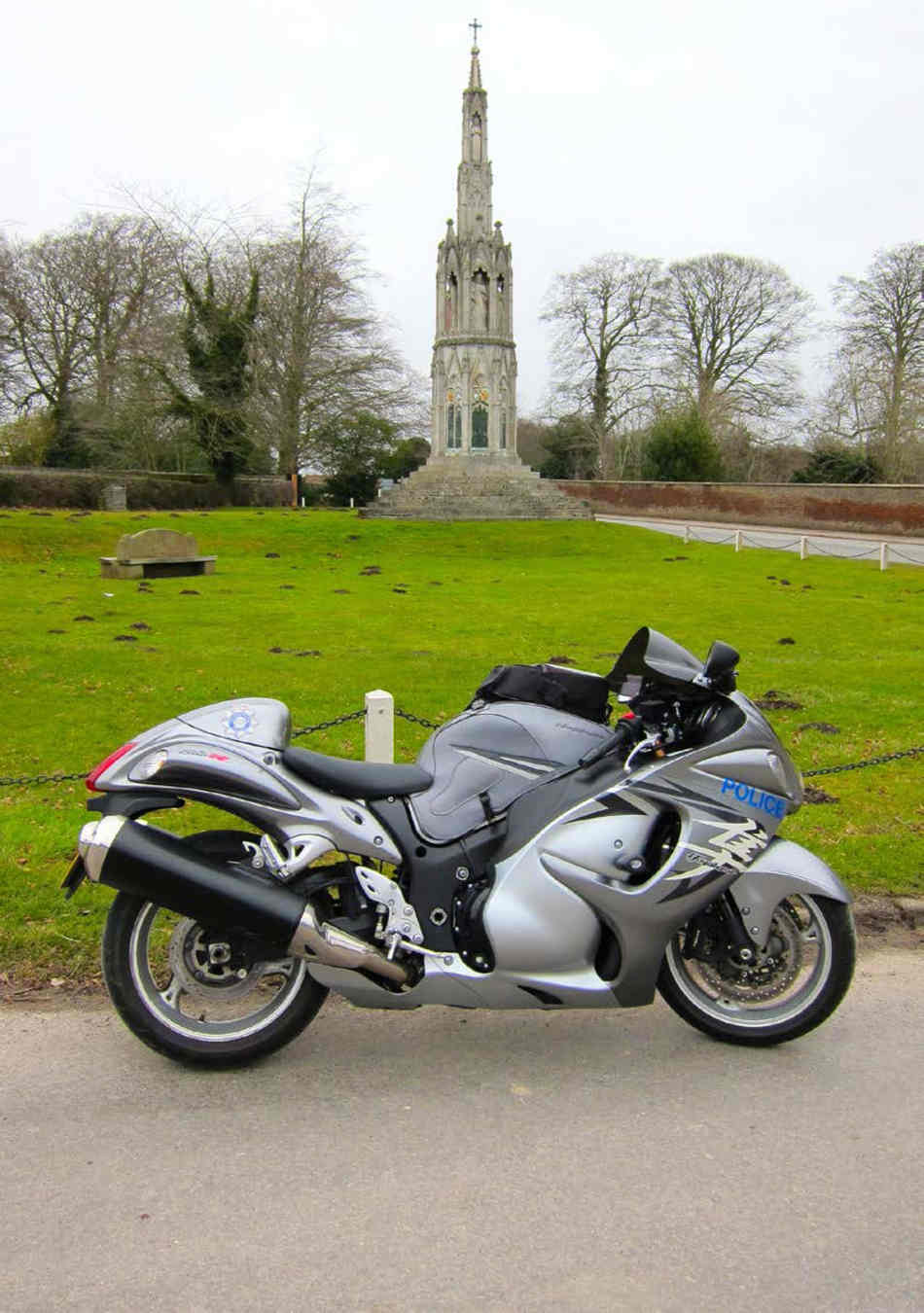 A Suzuki hayabusa, as described in the text, carrying police equipment, parked on a quiet road in front of a war memorial.