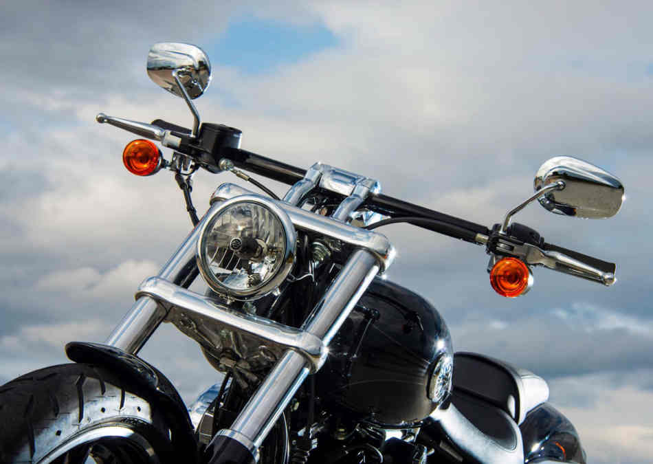 A close up of the tiny chrome headlight and black chrome flat handlebars, with small indicators and chrome mirrors, of the Breakout