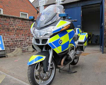A modern police BMW motorcycle, parked in front of a maintenance shed.