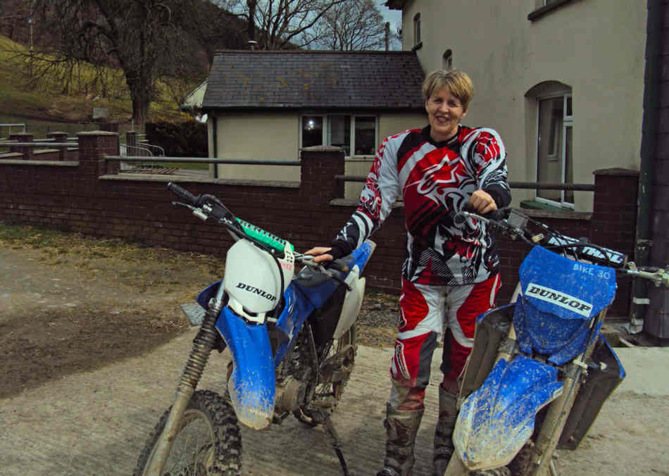 Jan standing between, a WR230 and WR450, wearing motocross gear