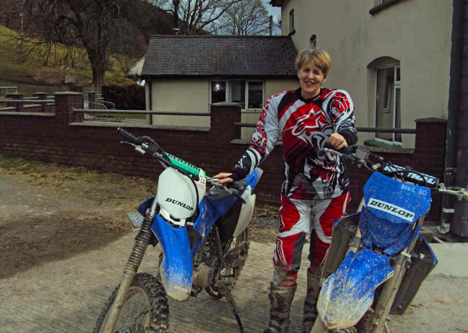 Jan standing between, a WR230 and WR450, wearing motocross gear