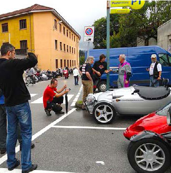 The Guzzi engined car parked up near the Guzzi factory, with lots of bystanders photographing it.