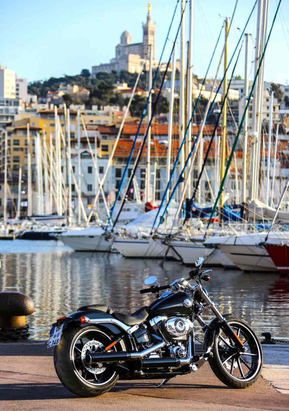 The Breakout parked on its sidestand on the seafront of a French harbour, with yachts moored in the background.