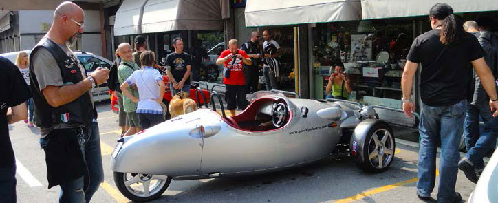 The Guzzi engined car parked in a shopping street being admired by some bikers.