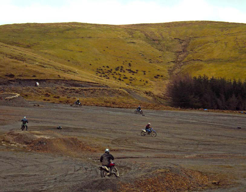 Five trainees riding round a windy shale track, with a hill in the background