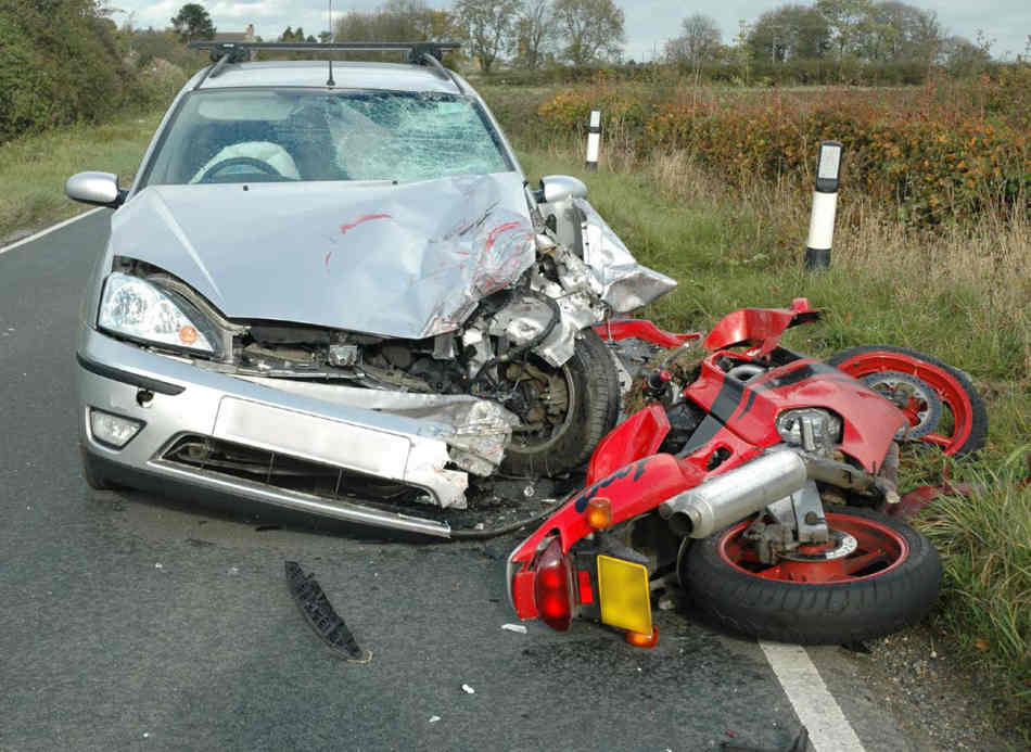 A Suzuki 1995 gsx 600F lying in its side, in front of a Ford Focus with a badly smashed wing, that the bike has hit.