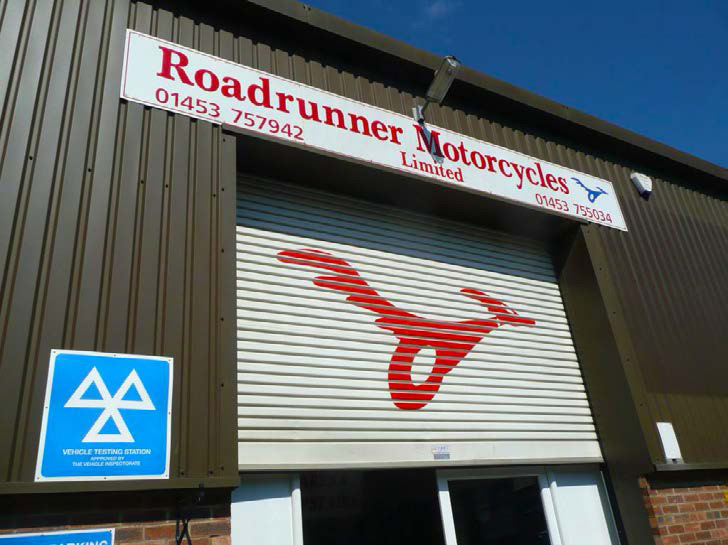 A view of the front of the Roadrunner premises, wit the security shutter part pulled down to display the Roadrunner logo painted on it.