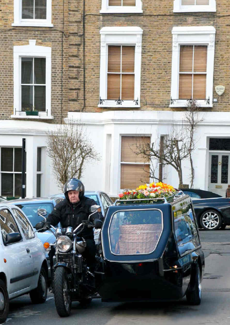 Motorcycle hearse containing Josh's wicker coffin being driven on a suburban London street