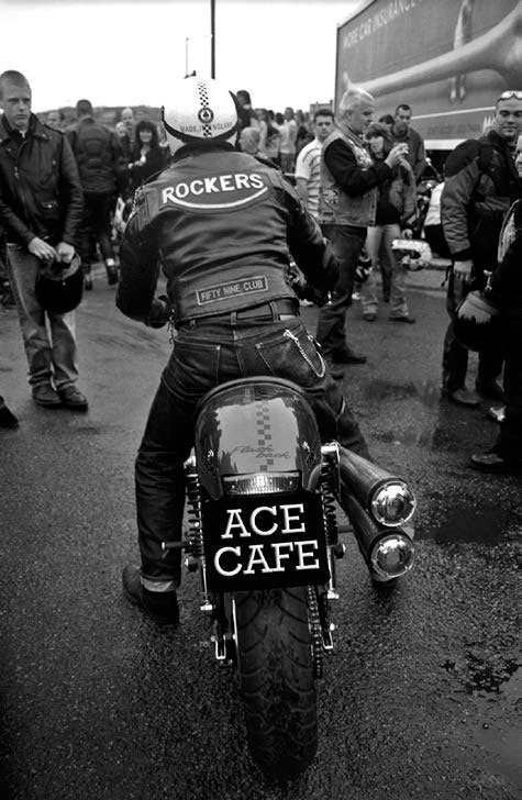 Rear view of a leather jacketed biker on a Cafe Racer in the car park of the Ace Cafe.