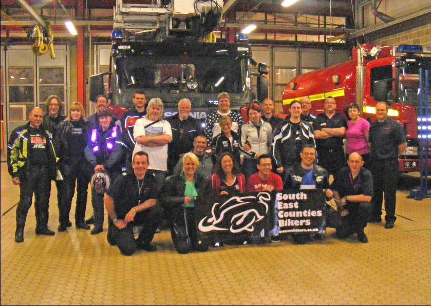 The South East Counties Bikers with the Biker Down team in a group portrait in the fire station, with the appliances behind them.