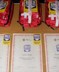 A close up shot of some of the Biker down certificates with first aid kits in the background.