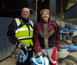 Jan and John, holding their helmets, standing in front of all the bikes, next to a barn.