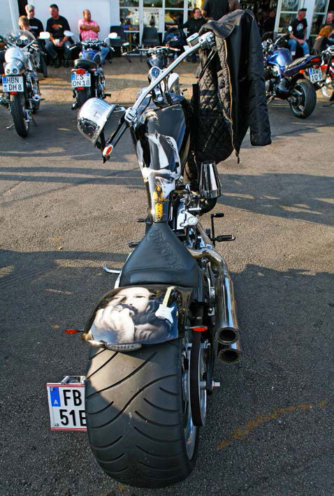 Rear view of a chopper motorcycle with a huge rear tyre, and a chrome plated German helmet hanging from the handlebars.