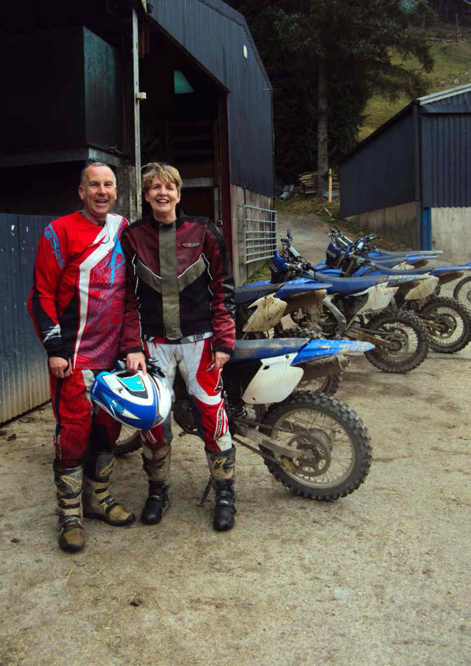 Jan and Geraint, Jan holding her helmet, standing in front of all the bikes, next to a barn.