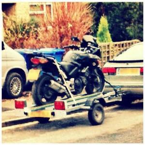 The black bike strapped onto a bike trailer, hooked onto the back of a Saab.