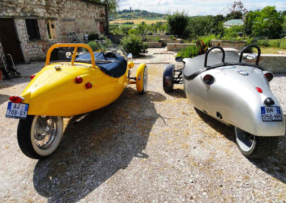 A rear view of both Avions parked on a gravel parking area in France on a sunny day.