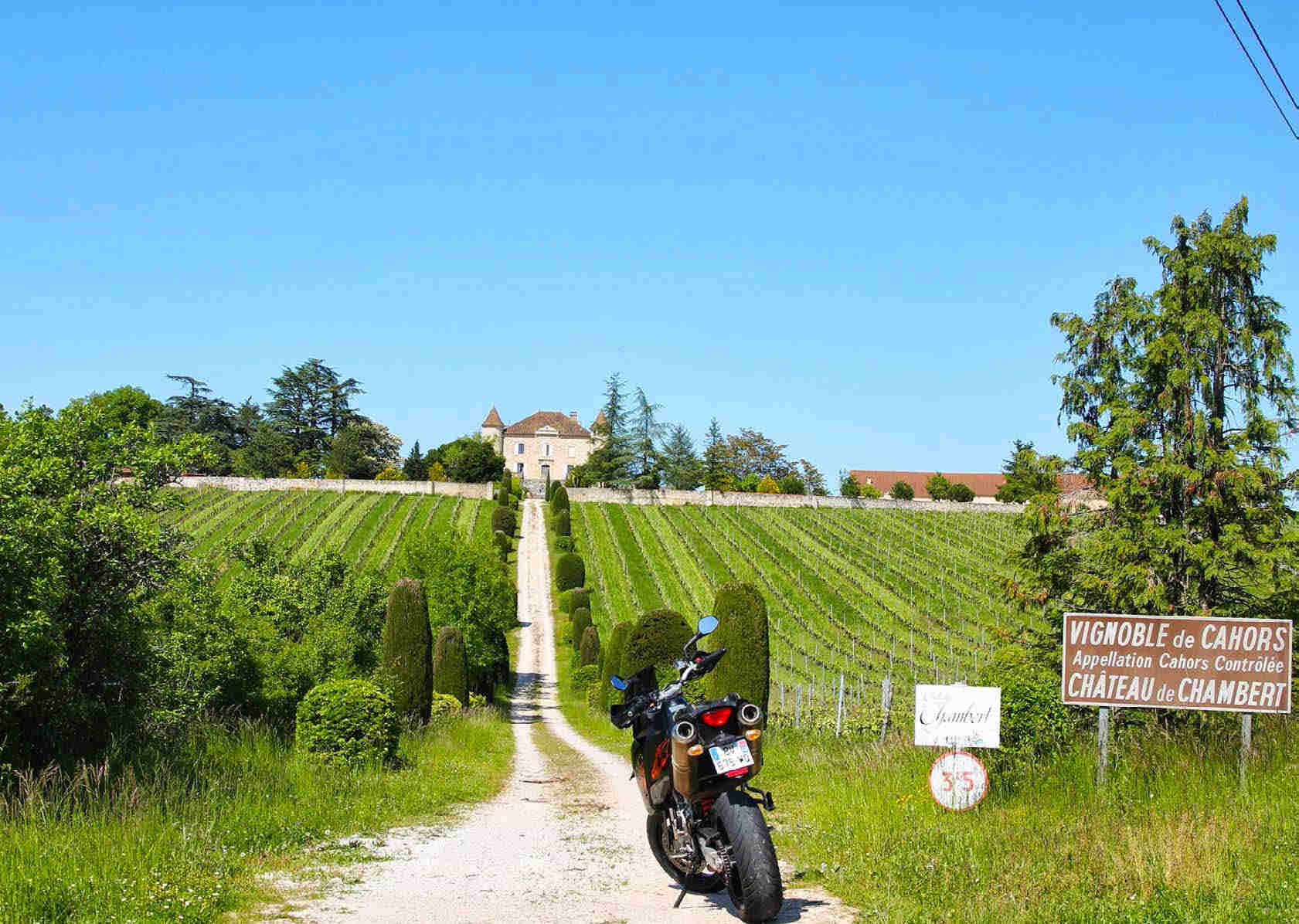 KTM parked at the start of the long gravel drive running up the  hill to the Chateau de Chambert, with vineyards either side.