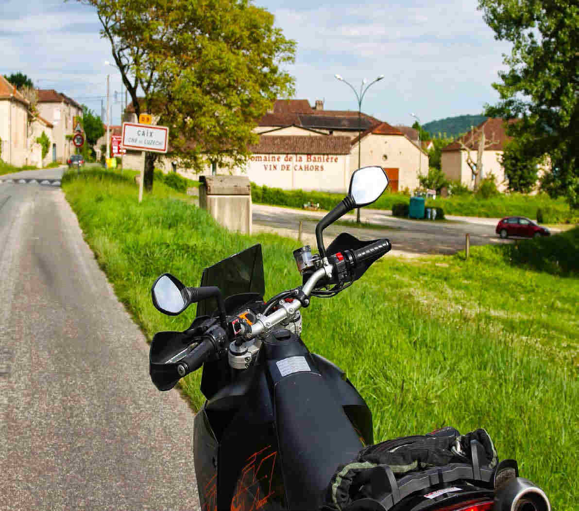 view over the handlebars of the parked KTM of the entrance to a small French village.