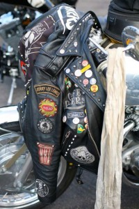Picture of a leather bike jacket covered in rocker badges hanging on the bars of a BSA Rocket Gold Star