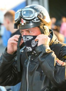 A biker wearing a vintage 'skid lid' helmet pulls a scarf over his mouth and nose before securing the strap of the helmet.