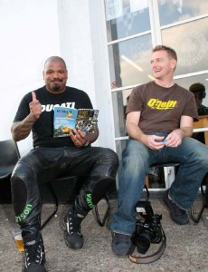 Two guys sitting outside on stools in front of the Ace front door, one wearing a Ducati t-shirt and leather bike jeans, giving a thumbs up while reading a copy of th10th anniversary Rider's Digest.