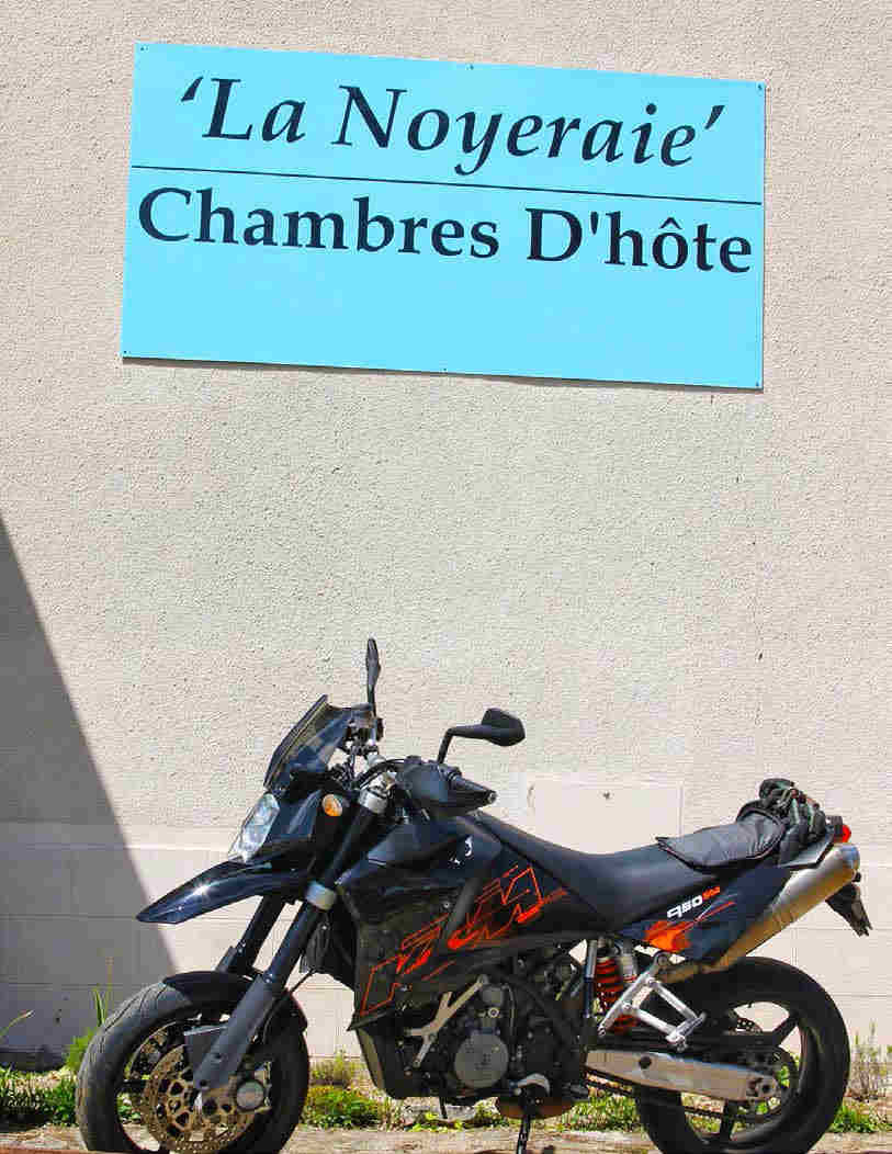KTM parked, viewed side on in the sun, with the hotel signboard, 'La Noyeraie', Chambres D'hote, behind it.