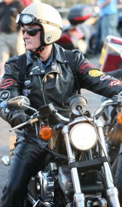 A quite middle aged biker on a Harley, wearing leathers, an open face helmet,  and dark glasses.
