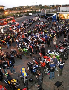 An view from above of a large group of bikes parked outside the Ace, with crowds of bikers and onlookers.