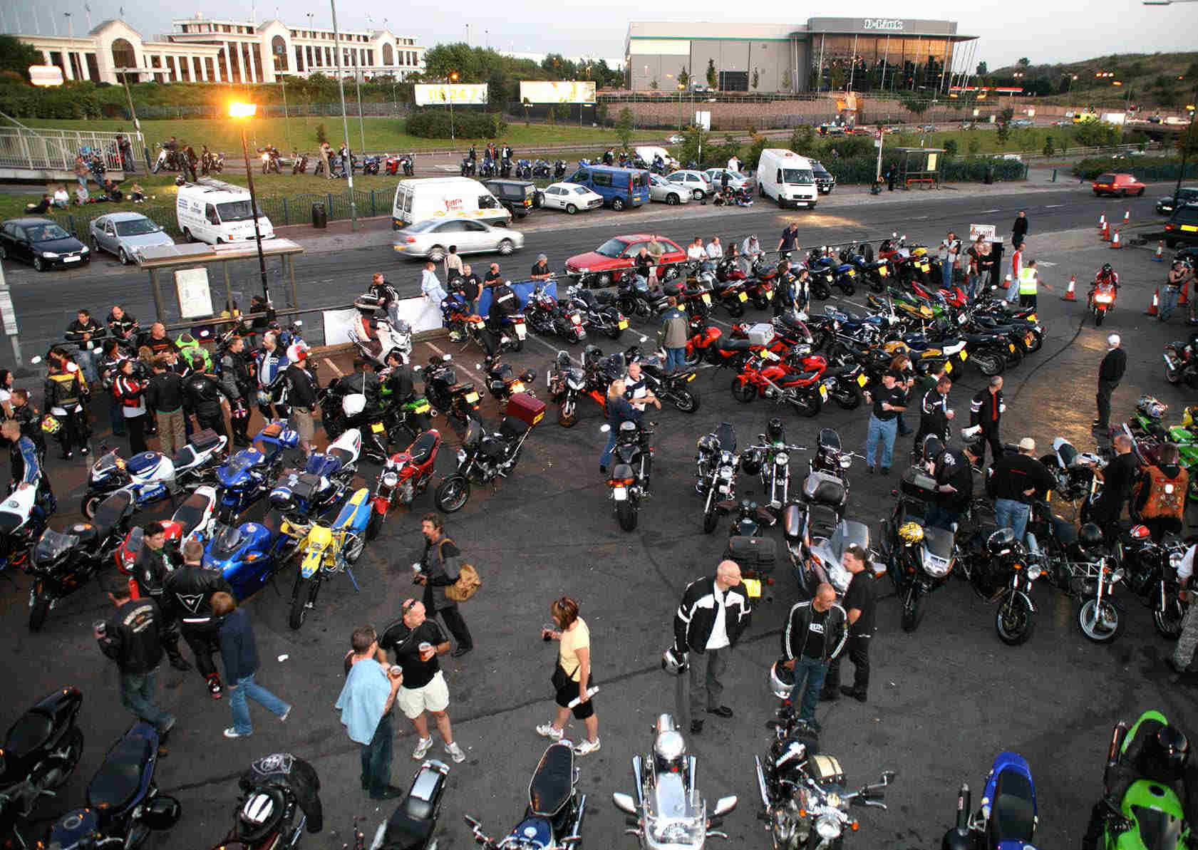 The car park of the Ace, crowded with bikes and strolling pedestrians looking at them.