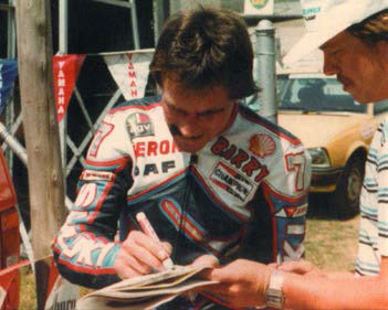Barry signing an autograph, wearing racing leathers.