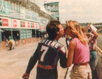 Barry, wearing leathers, and no helmet, in front of the pits, kissing his girlfriend.
