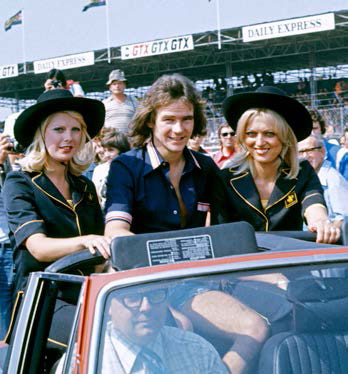 Barry on a victory parade, standing in the back of a Triumph Stag, with a paddock girl either side.
