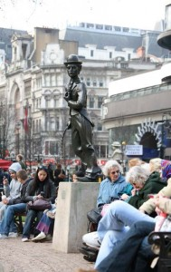 People sitting on benches in London next to a statue of Charlie Chaplin