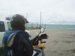 View of the shoulder of a parked biker looking out to sea over a cold beach