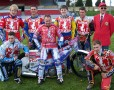 Speedway team standing round and sitting on a bike